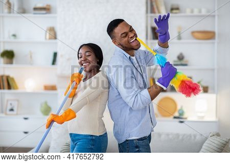 Joyful Black Man And His Girlfriend Singing During Housecleaning, Using Mop And Duster As Microphone