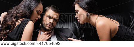 Young Man Looking At Camera While Sensual Women Seducing Him Isolated On Black, Banner.