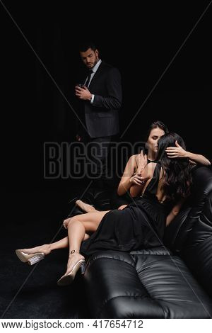 Seductive Women Hugging On Leather Couch Near Man With Glass Of Whiskey Isolated On Black.
