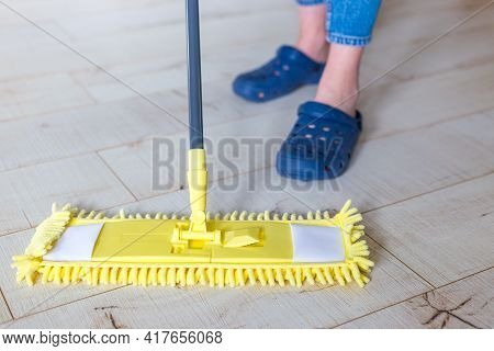 Woman Cleaning Floor With Yellow Mop At Home. Microfiber Mop Isolated On White Wooden Floor Backgrou