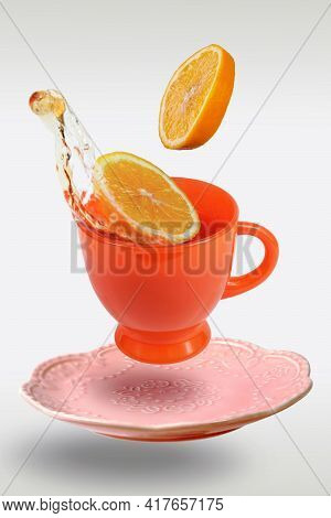 Levitating Orange Teacup And Saucer With Tea And Lemon Slices