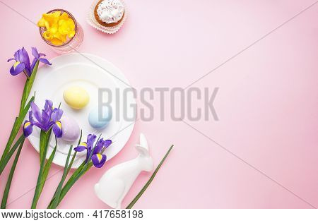 Easter Holiday Table Setting And Plates With Colorful Eggs On A Pink Background. Easter Holiday Conc