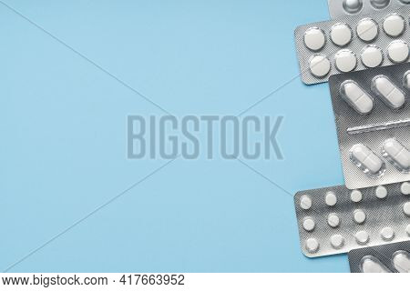 Packs Of White Pills On Blue Background, Top View. Different Medicines, Tablets, Medicine Capsules.