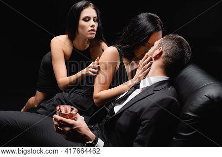 Passionate Brunette Women Seducing Businessman Holding Glass Of Whiskey Isolated On Black.