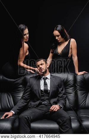 Sexy Women Seducing Businessman Sitting On Leather Couch Isolated On Black.