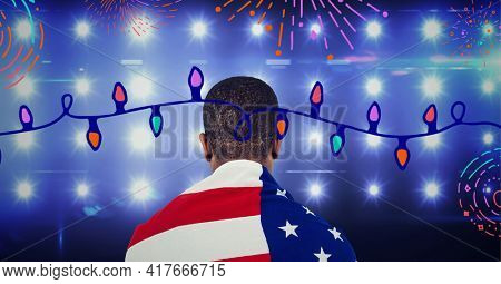 Composition of fireworks and fairy lights with man wrapped in american flag over stadium spotlights. american patriotism, celebration and sport concept digitally generated video.