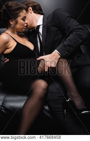 Passionate Man In Suit Seducing Sexy Woman In Slip Dress Sitting On Sofa On Black.