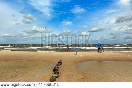 Cyclist with a bicycle stands on the beach and looks into the distance