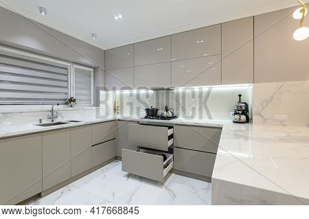 Open drawers at well designed large modern white wood and marble kitchen, some drawers pulled out