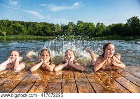 Happy little girls having fun playing in a lake splashing water during summer holidays