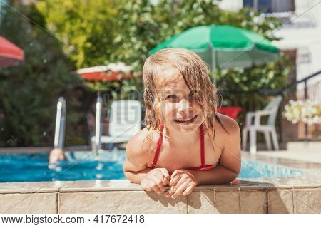 Happy little girl having fun playing in outdoor pool splashing water during summer holidays