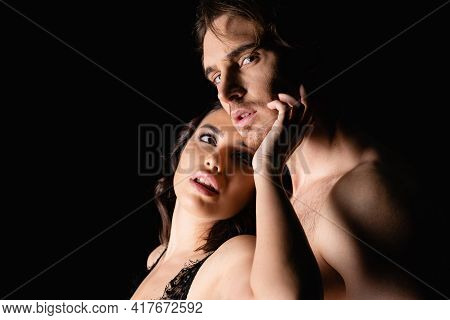 Sexy Woman Embracing Shirtless Man Isolated On Black.