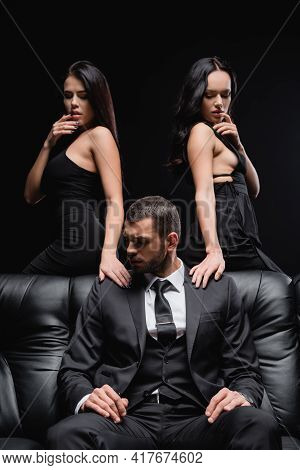 Flirty Women Seducing Young Businessman Sitting On Leather Couch Isolated On Black.