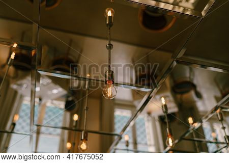 Mirrored Ceiling With Retro Light Bulbs In The Interior Of The Restaurant.