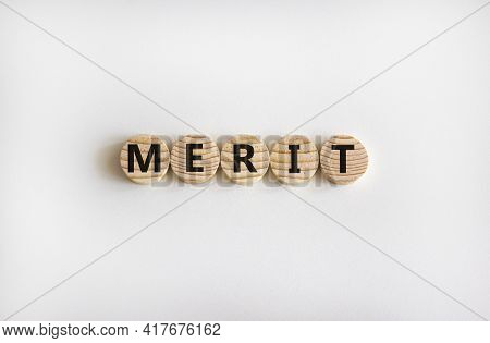 Merit Symbol. Wooden Circles With The Word 'merit'. Beautiful White Background, Copy Space. Business