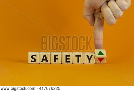 Safety Level Symbol. Businessman Turns A Cube And Changes The Expression 'safety Down' To 'safety Up