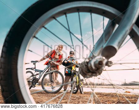 Caucasian Happy Mother And Son Riding Together And Posing For Photo. View From Bicycle Wheel, Family
