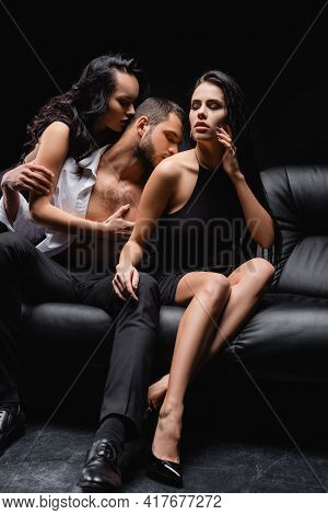 Seductive Women Sitting On Leather Couch Near Lovers Isolated On Black.
