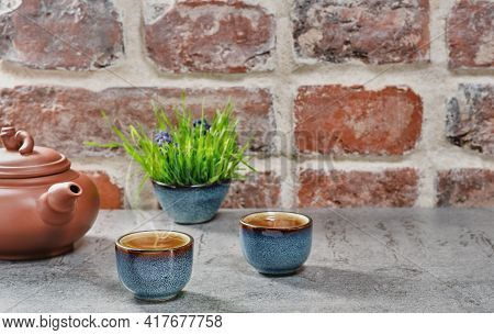 Two Cups With Green Matcha Tea On Gray Stone Table, Selective Focus. Ceramic Teapot With Tea, Steam