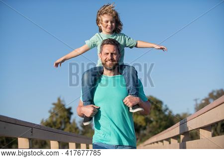 Handsome Father Piggybacking Son Playing On Nature, Daddy Holding Riding On Back Adorable Cheerful K