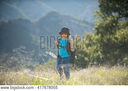 Kid With Backpack Hiking In Mountains. Boy Local Tourist Goes On A Local Hike.