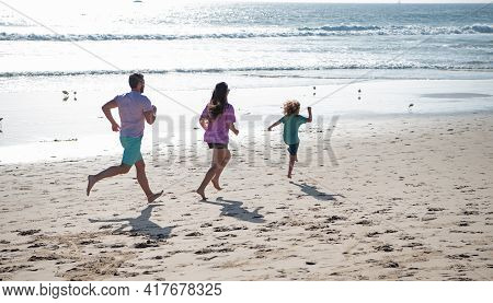 Family Running On A Sandy Beach. Concept Of Friendly Family Jogging Outdoors. Active Parents And Peo