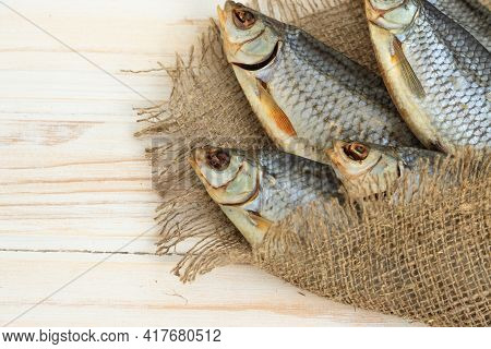 Dry Roach Fish Lies On A Wooden Table View From Above.