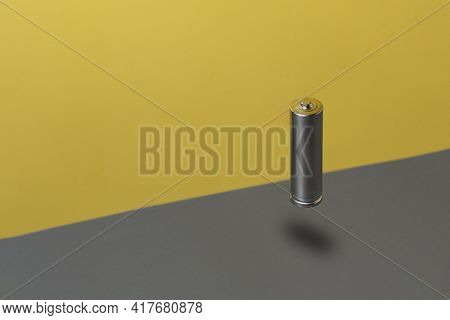 Flying Alkaline Rechargeable Battery Against Grey And Yellow Background. Minimal Electronic Concept