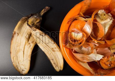 Banana Peels And Other Peels From Kitchen In Orange Plate, On Black Background, Close Up.