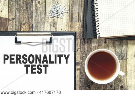 Text Written On White Paper, Personality Test. The Sheet Is On A Wooden Table, Next To It Is A Cup O