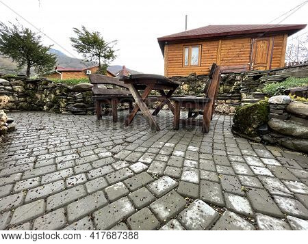 Close Up Of Wooden Table With Benches In Countryside. Log Table And Benches In Empty Village In Clou