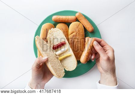Fresh Hot Dog Buns Which Lie On A Green Plate Along With Sausages. The Girl Holds In Her Hands A Bun