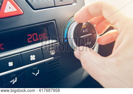 Man Hand Set The Temperature Of Air Conditioner In The Car. Driver Turning On Car Climate Control Sy