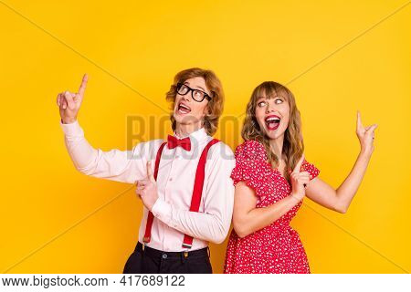 Photo Portrait Of Cheerful Lovely Couple Showing Fingers Up Advert Promo Isolated On Vivid Yellow Ba