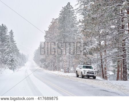 Fort Collins, CO, USA - April 19, 2021: Toyota 4RUnner SUV (2016 Trail model) in a heavy springtime snowstorm in the Poudre River Canyon  in Colorado Rocky Mountains, winter travel concept.