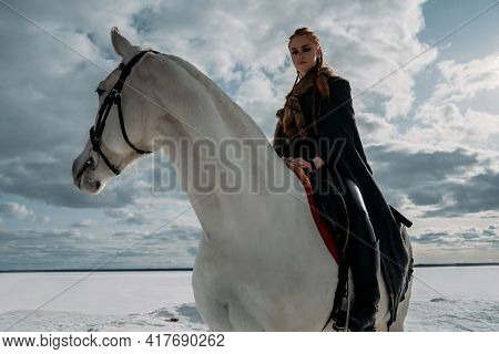 Young Viking Woman With Red Hairs Ride A Horse. Dramatic Light. Role-playing Game