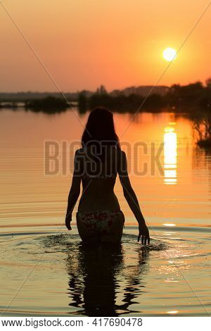 Sunset. Silhouette Of A Girl. Girl Plays With Spray With Water In The River.