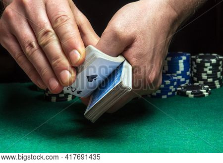 Close-up Hands Of A Person-dealer Or Croupier Shuffling Poker Cards In A Poker Club On The Backgroun