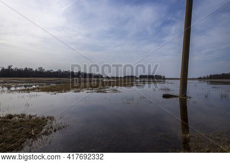 Electric Transmission Line Support Against The Background Of The Landscape. A Flooded Field On The O