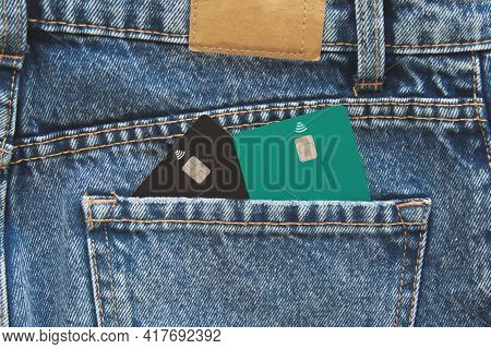 Two Credit Plastic Cards With A Chip Black And Green In The Back Pocket Of Blue Jeans