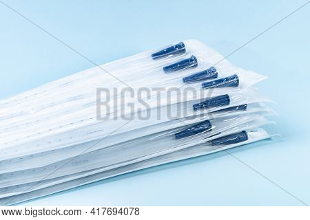 Rusch Male And Female All Purpose Catheter On Blue Background, Straight Tipped Intermittent Catheter
