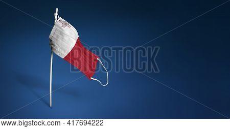 Malta Mask On Dark Blue Background. Waving Flag Of Malta Painted On Medical Mask On Pole. Concept Of