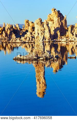Mono Lake is a salt lake in California. Lime-tuff towers of bizarre shapes rise from the bottom of the lake. Magic sunrise. Magic reflections of tuff outliers in lake water.