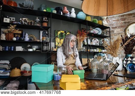Beautiful Aged Woman In Eyeglasses And Apron Sitting At Counter And Working On Modern Laptop. Pretty
