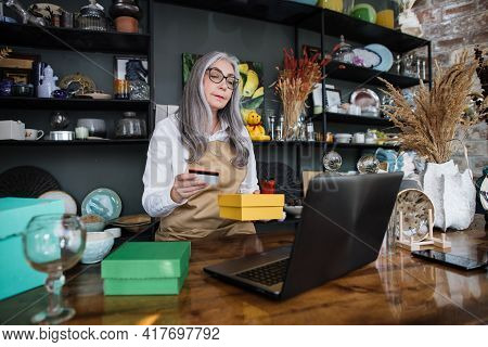 Professional Aged Woman Holding Discount Card And Yellow Box While Sitting At Decor Store. Saleswoma