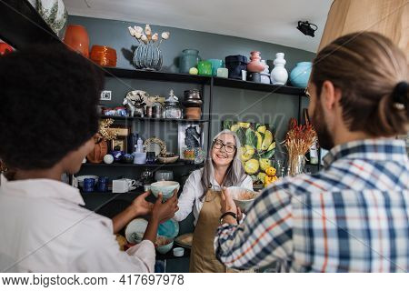 Back View Of Young Multiracial Couple In Casual Wear Buying Goods At Decor Shop. Pleasant Aged Sales