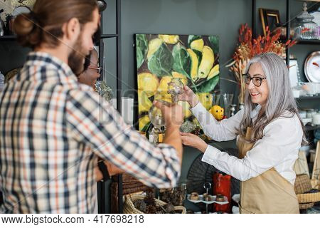 Competent Mature Saleswoman In Beige Apron Showing Various Goods At Store For Young Multiracial Coup