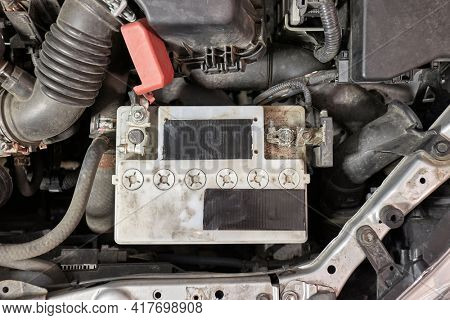 Old car starter battery inside the engine bay viewed from above top down