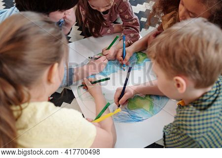 Group of children sitting at the table and drawing a picture with colored pencils together