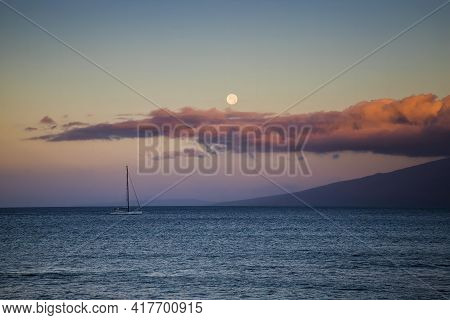 Moon Setting As Dawn Arrives Over Pacific Ocean With Pink Clouds And A Catamaran Boat On Horizon.